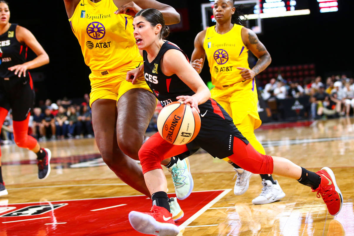 Las Vegas Aces' Kelsey Plum, center, drives to the basket against Los Angeles Sparks' Kalani Br ...