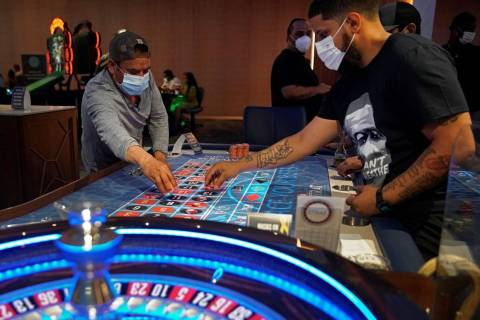 People wear face masks as they play roulette on the Fourth of July at the Strat hotel-casino in ...