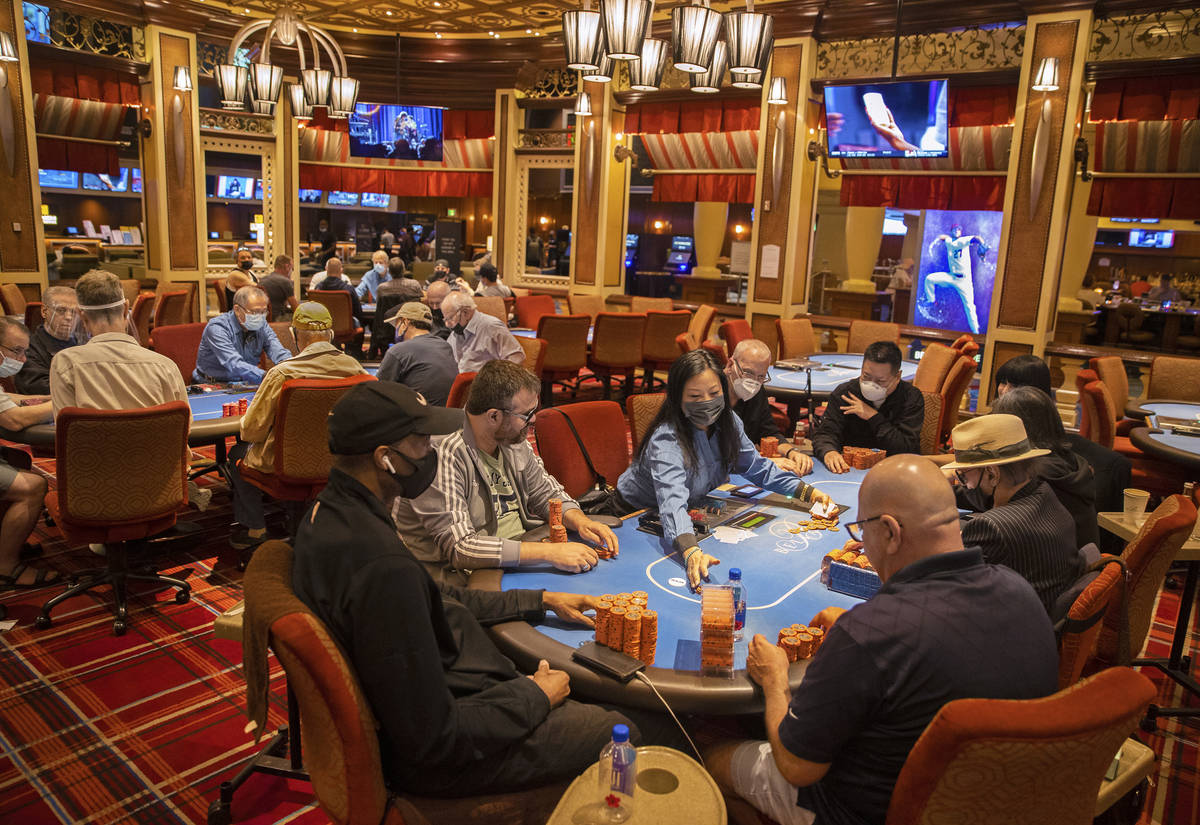 The poker tables at Bellagio are packed, with plexiglass barriers having recently been removed, ...