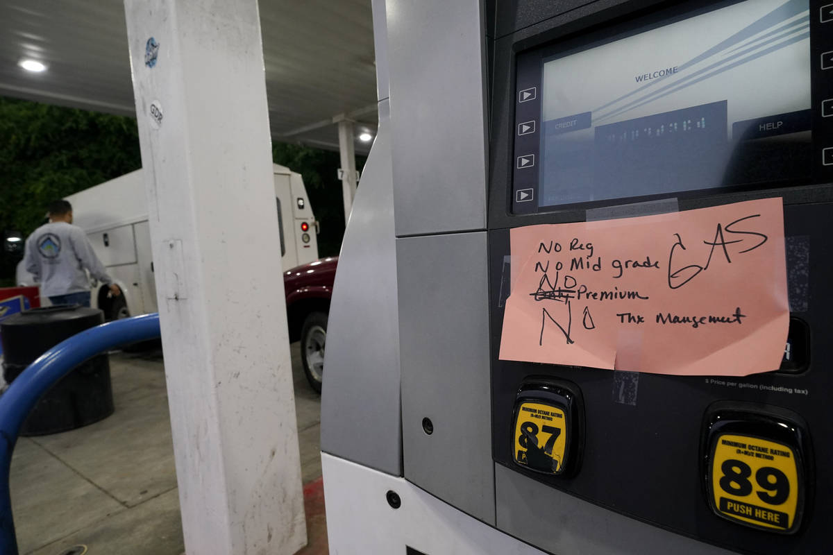A hand written sign is posted on a gas pump, showing that the service station is out of all gra ...