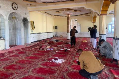 Afghan journalist take photos and film inside a mosque after a bomb explosion in Shakar Dara di ...