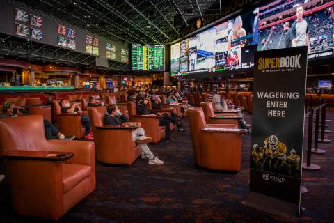 People watch events as the Westgate sportsbook posts hundreds of Super Bowl prop bets Jan. 28 i ...