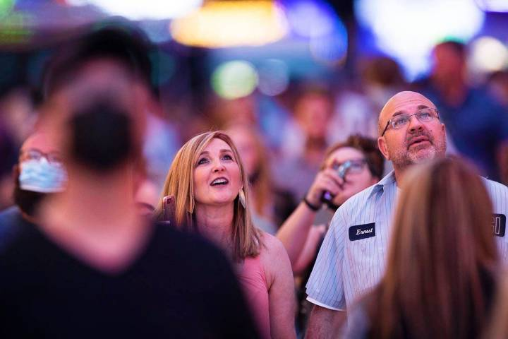 Maskless people walk through the Fremont Street Experience on Thursday, May 13, 2021, in Las Ve ...