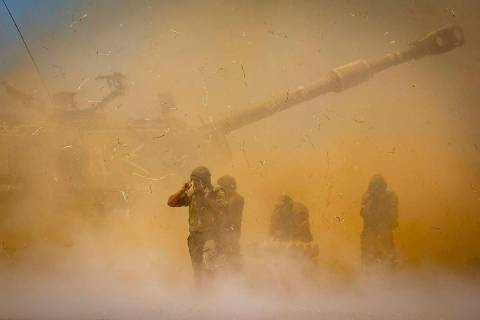 An Israeli artillery unit fires toward targets in Gaza Strip, at the Israeli Gaza border, Wedne ...