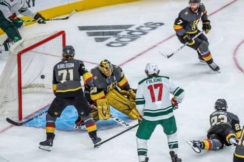 The puck gets past Golden Knights goaltender Marc-Andre Fleury (29) as Minnesota Wild center Jo ...