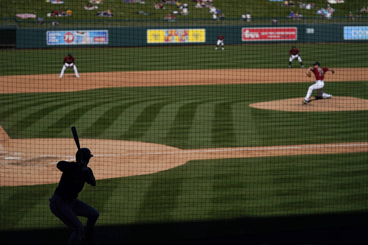 Milwaukee Brewers' Zach Green, left, gets ready for his at-bat in the shade as Arizona Diamondb ...