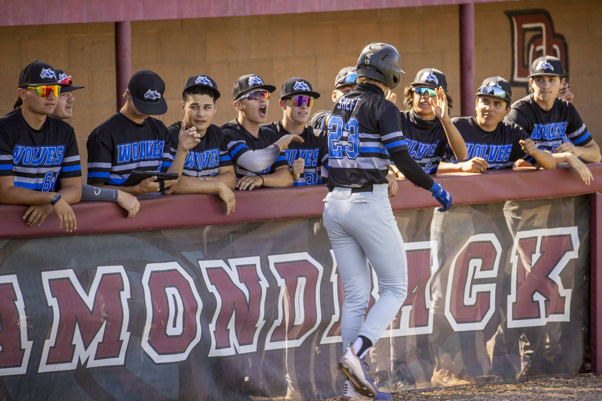 Basic runner Cooper Sheff (23) helps celebrate a run with teammates against Basic High School d ...