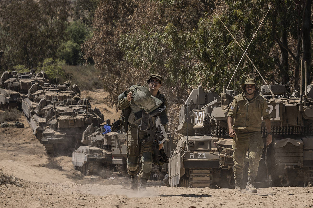 Israeli soldiers gather at a staging ground near the border with the Gaza Strip, in southern Is ...