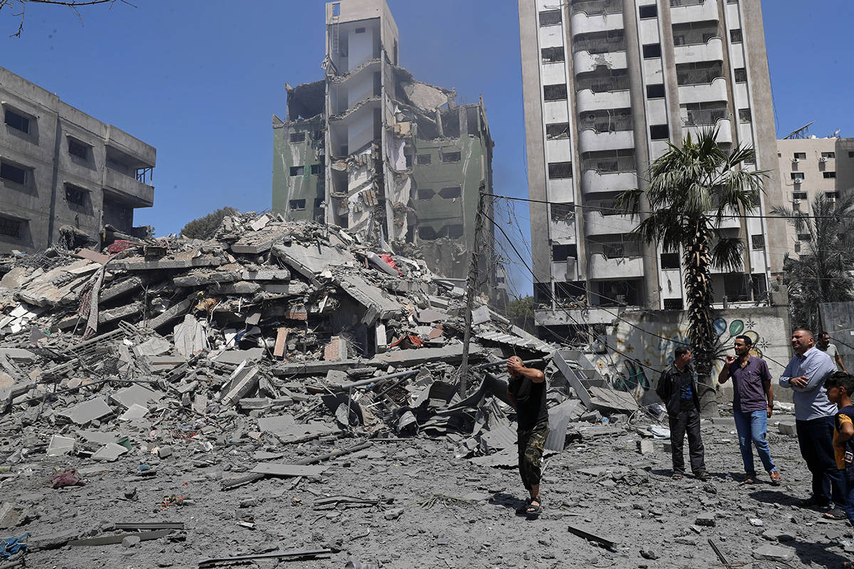People inspect the rubble of a destroyed residential building that was hit by an Israeli airstr ...