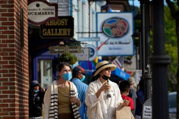 Visitors walk on a busy sidewalk, Saturday, May 15, 2021, in Bar Harbor, Maine. Gov. Janet Mill ...