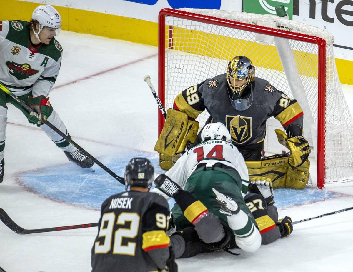 Golden Knights goaltender Marc-Andre Fleury (29) defends the net as Minnesota Wild center Joel ...