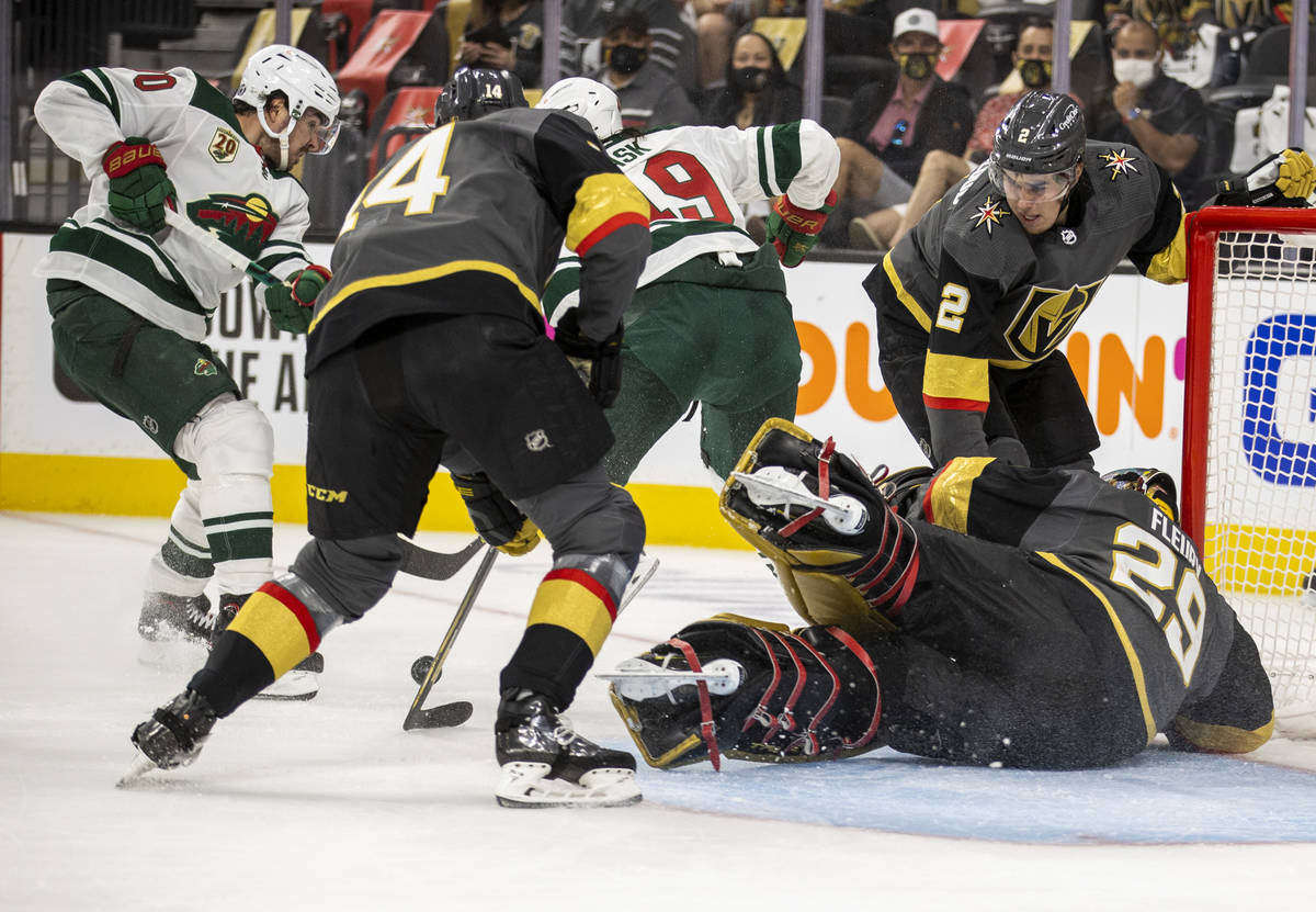 Golden Knights goaltender Marc-Andre Fleury (29) dives to the ice to assist teammate defenseman ...