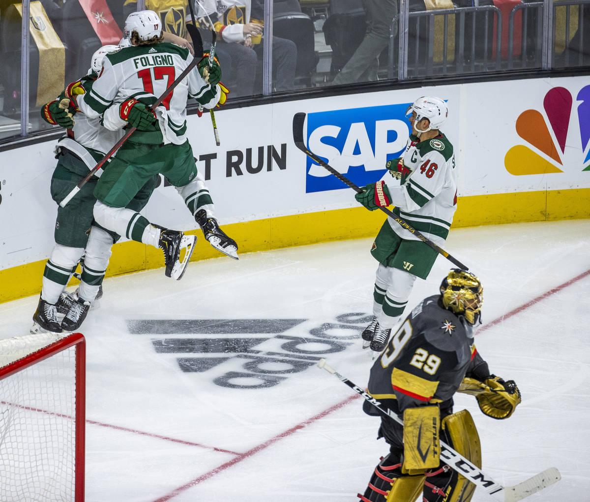 Minnesota Wild players celebrate their winning goal as Golden Knights goaltender Marc-Andre Fle ...