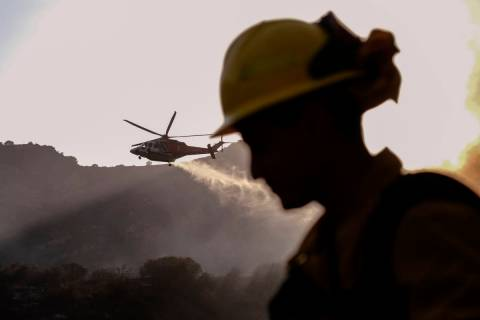A firefighter keeps watch as a firefighting helicopter drops water on a brush fire scorching at ...