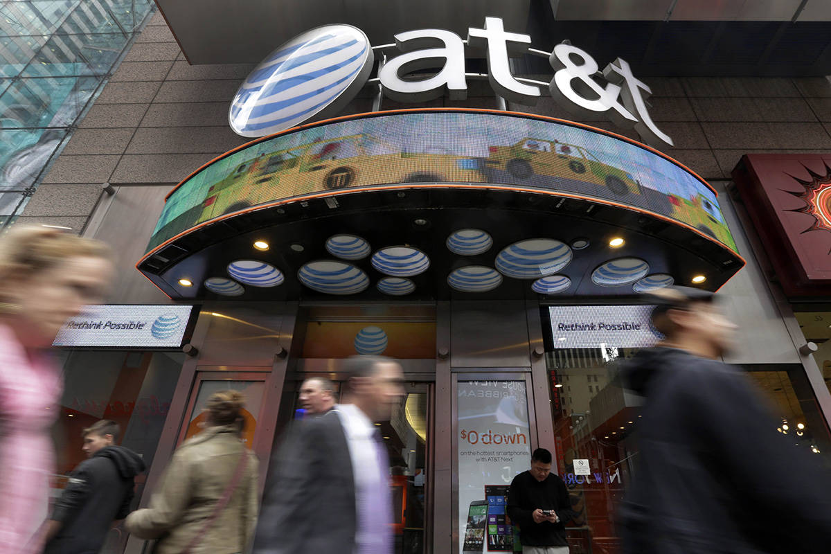 FILE - In this Oct. 21, 2014 file photo, people pass an AT&T store in New York's Times Squa ...