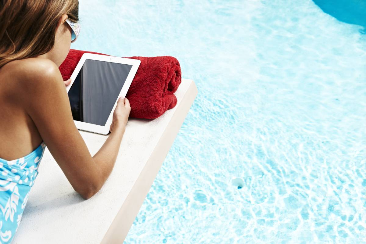 A guest holding an iPad while lounging at a pool. (Courtesy, MGM Resorts International)