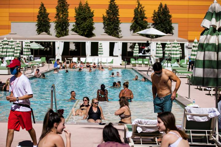 Guests lounge by the pool at Park MGM on Saturday, March 6, 2021, in Las Vegas. (Benjamin Hager ...