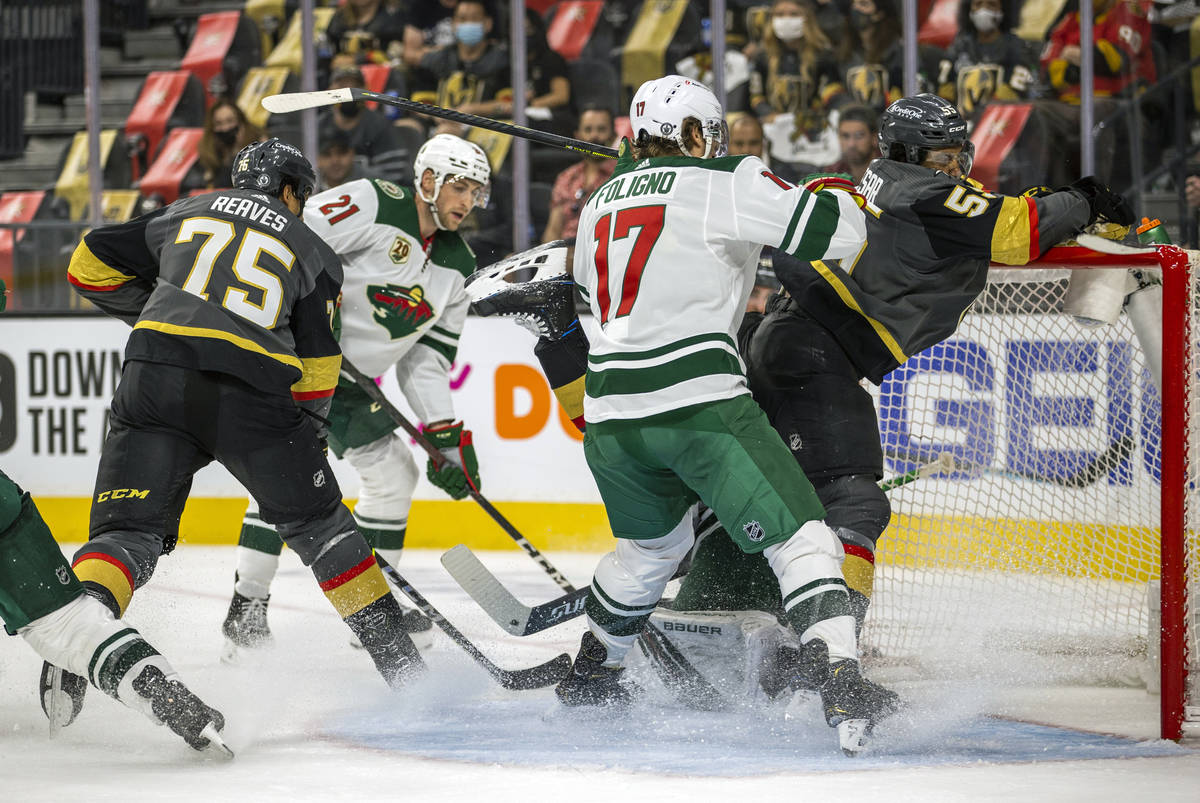 (From right) Golden Knights right wing Keegan Kolesar (55) is driven into the net by Minnesota ...