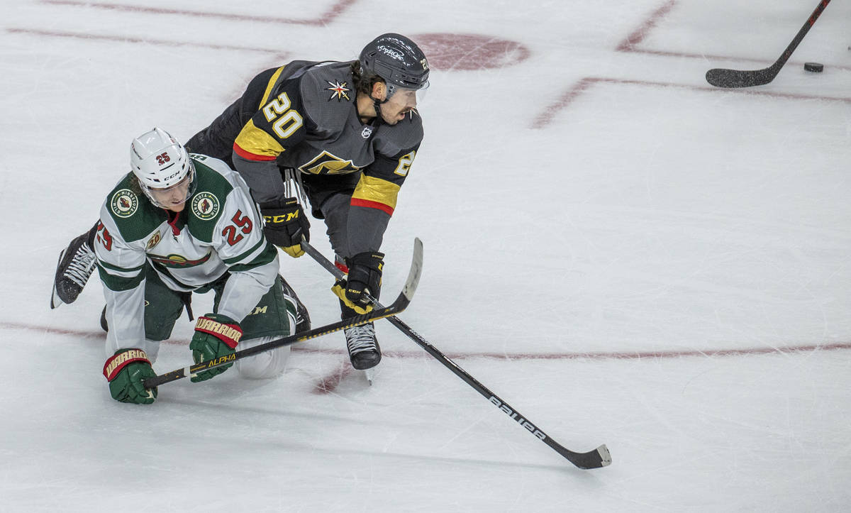 Golden Knights center Chandler Stephenson (20) eyes the puck as he tumbles over Minnesota Wild ...