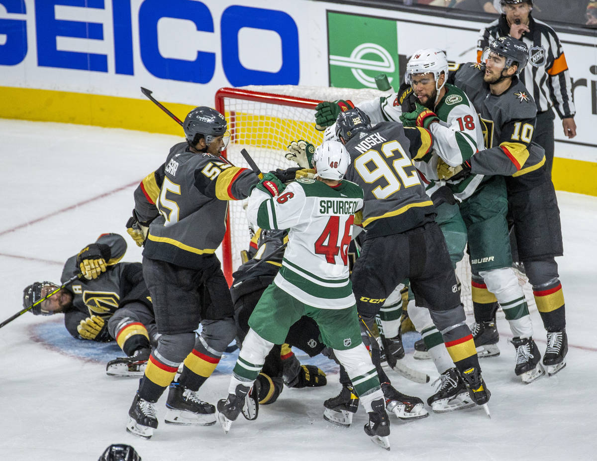 Golden Knights and Minnesota Wild players fight during the third period of an NHL playoff game ...