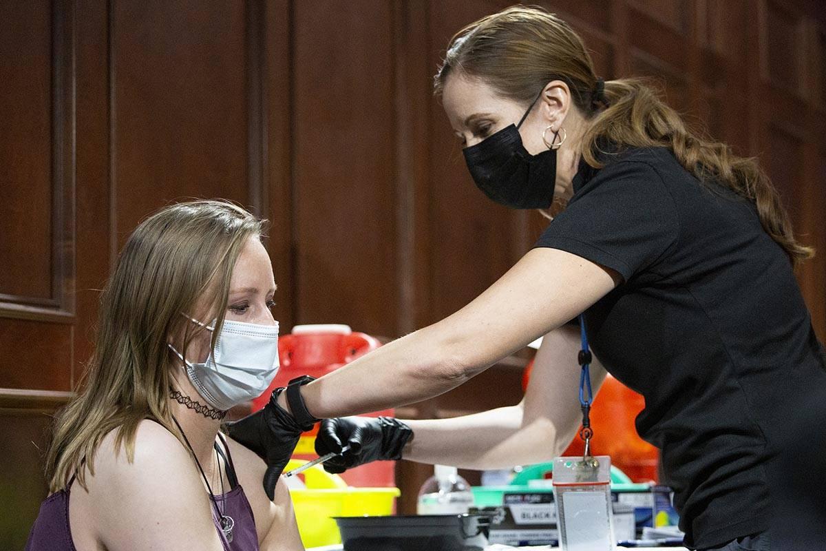 Savannah Wilkinson receives the Pfizer vaccine from Sarah Lugo, senior community health nurse w ...
