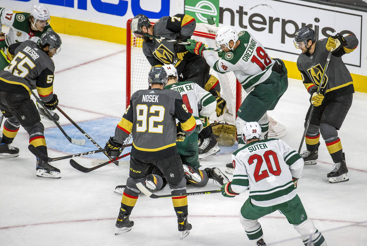 Golden Knights and Minnesota Wild players battle near the net during the third period of an NHL ...