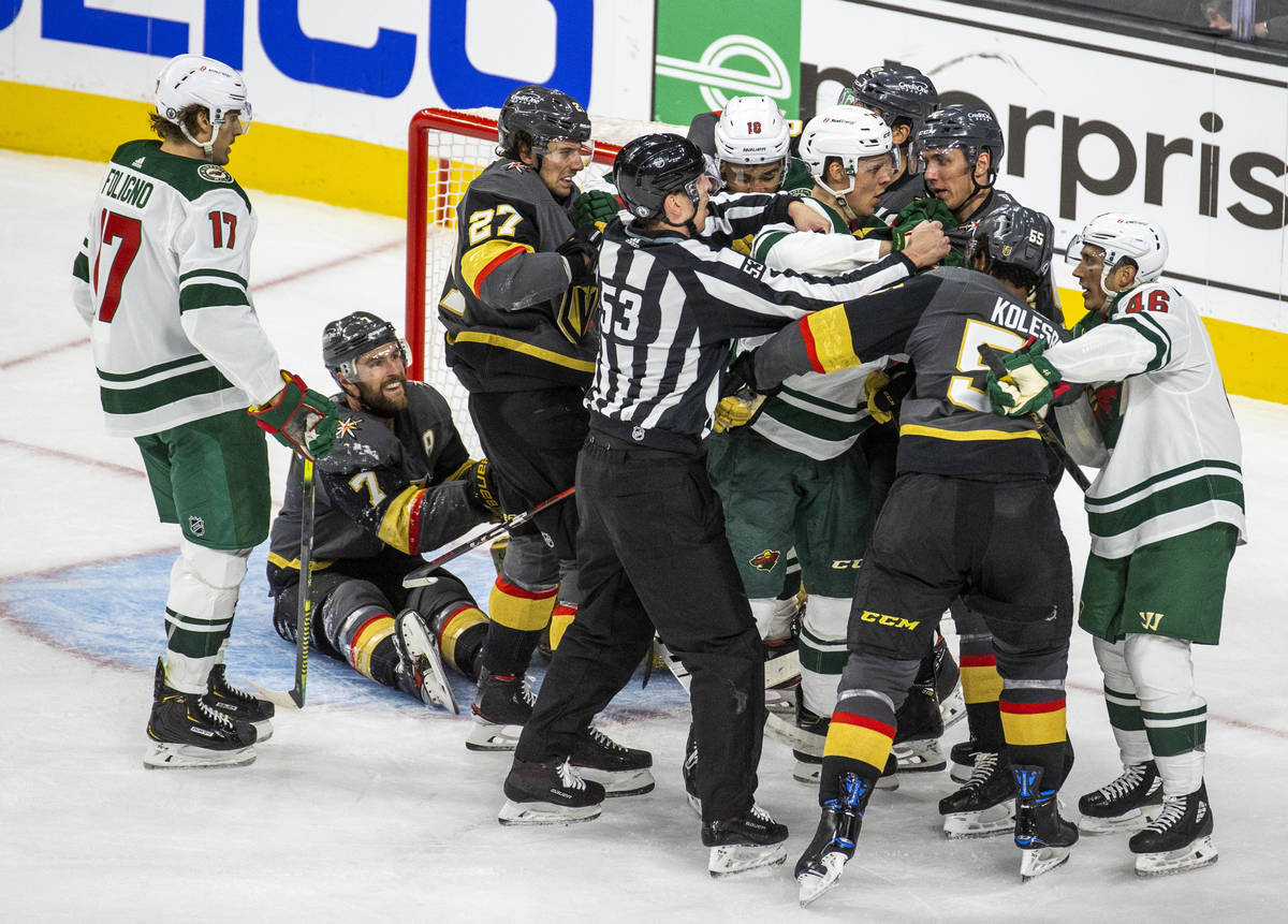 Golden Knights and Minnesota Wild players fight near the net during the third period of an NHL ...