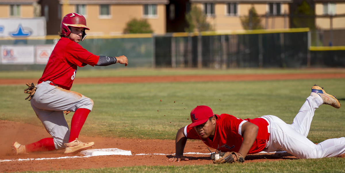 Arbor View runner Seth Parr (8) makes it to third base safely as Liberty infielder Keoni Young ...