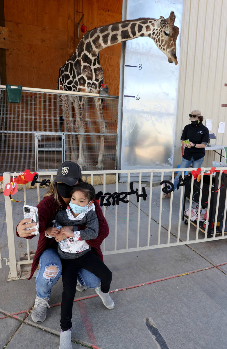 Ozzie the giraffe poses for a photo with Garlene Lao and her daughter Gianna Lao, 4, during a w ...