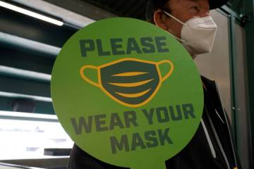 A stadium worker holds up a sign for people to wear face masks before a baseball game between t ...