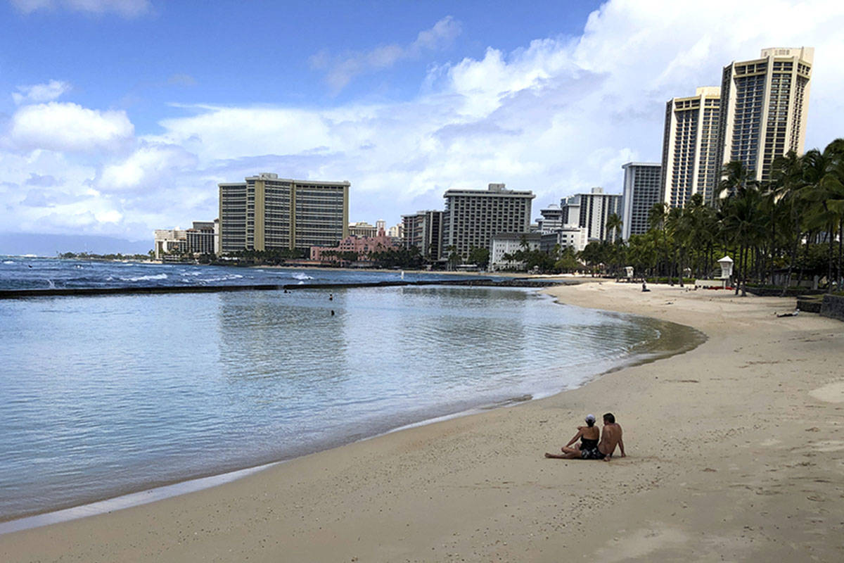 A couple rests on an empty section of Waikiki Beach in Honolulu in March 2020. (AP Photo/Caleb ...