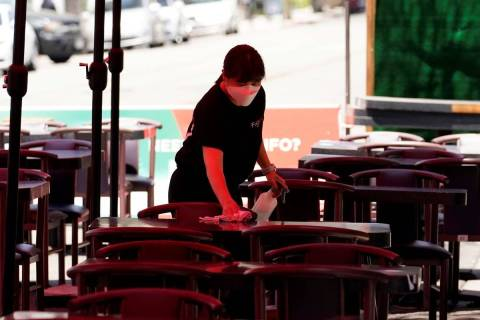 Tables are cleaned in an outdoor eating area amid the COVID-19 pandemic Tuesday, May 18, 2021, ...