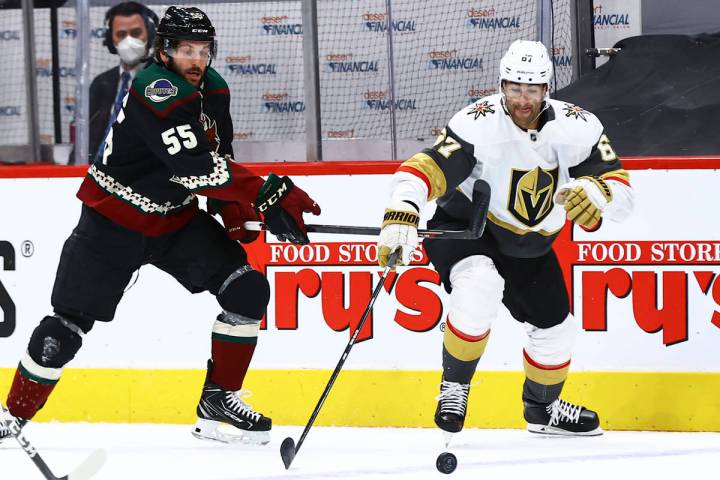 Golden Knights' Max Pacioretty (67) reaches out for the puck under pressure from Arizona Coyote ...