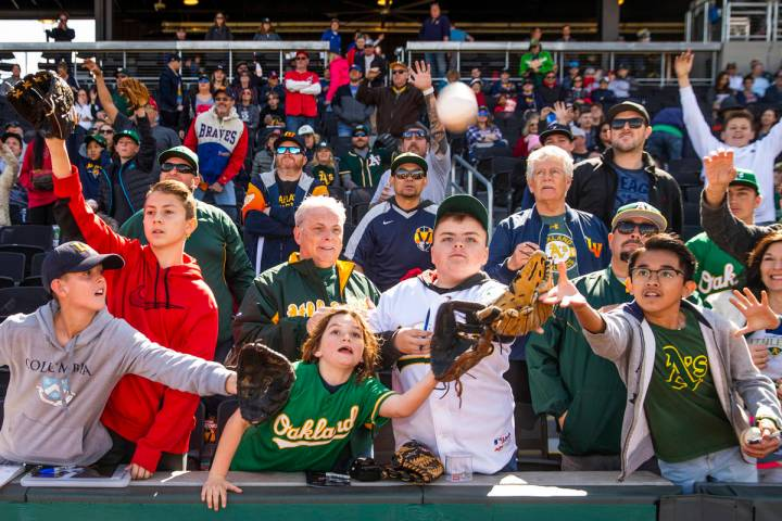 Fans work for position to catch a ball tossed by an Oakland Athletics player during a Big Leagu ...
