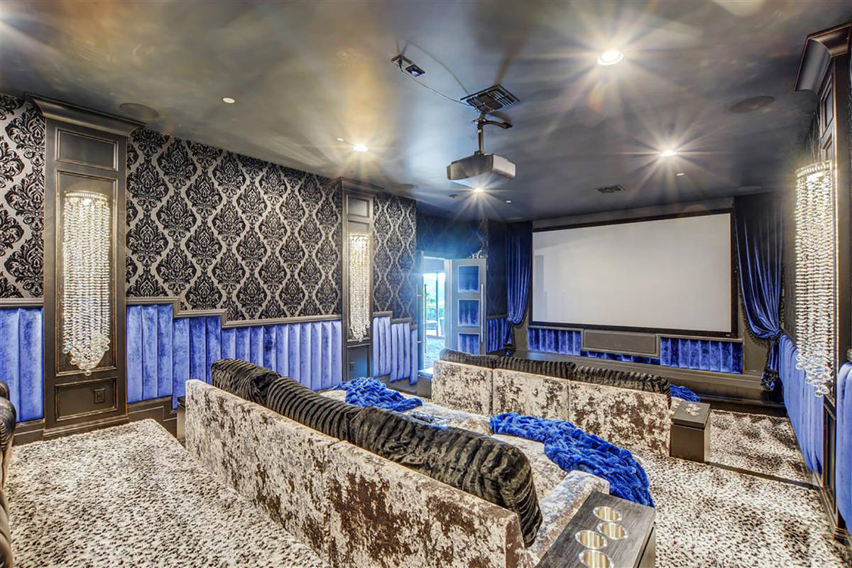 A home theater has 12 seats and lounging couches while a game room next to it with vintage pinb ...