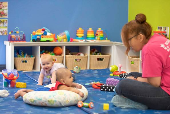 Lorenzo smiles at Miss Brenda while Zoe plays in the background at Rising Star Preschool & ...