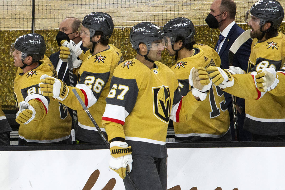 Golden Knights left wing Max Pacioretty (67) and Golden Knights right wing Mark Stone (61) fist ...