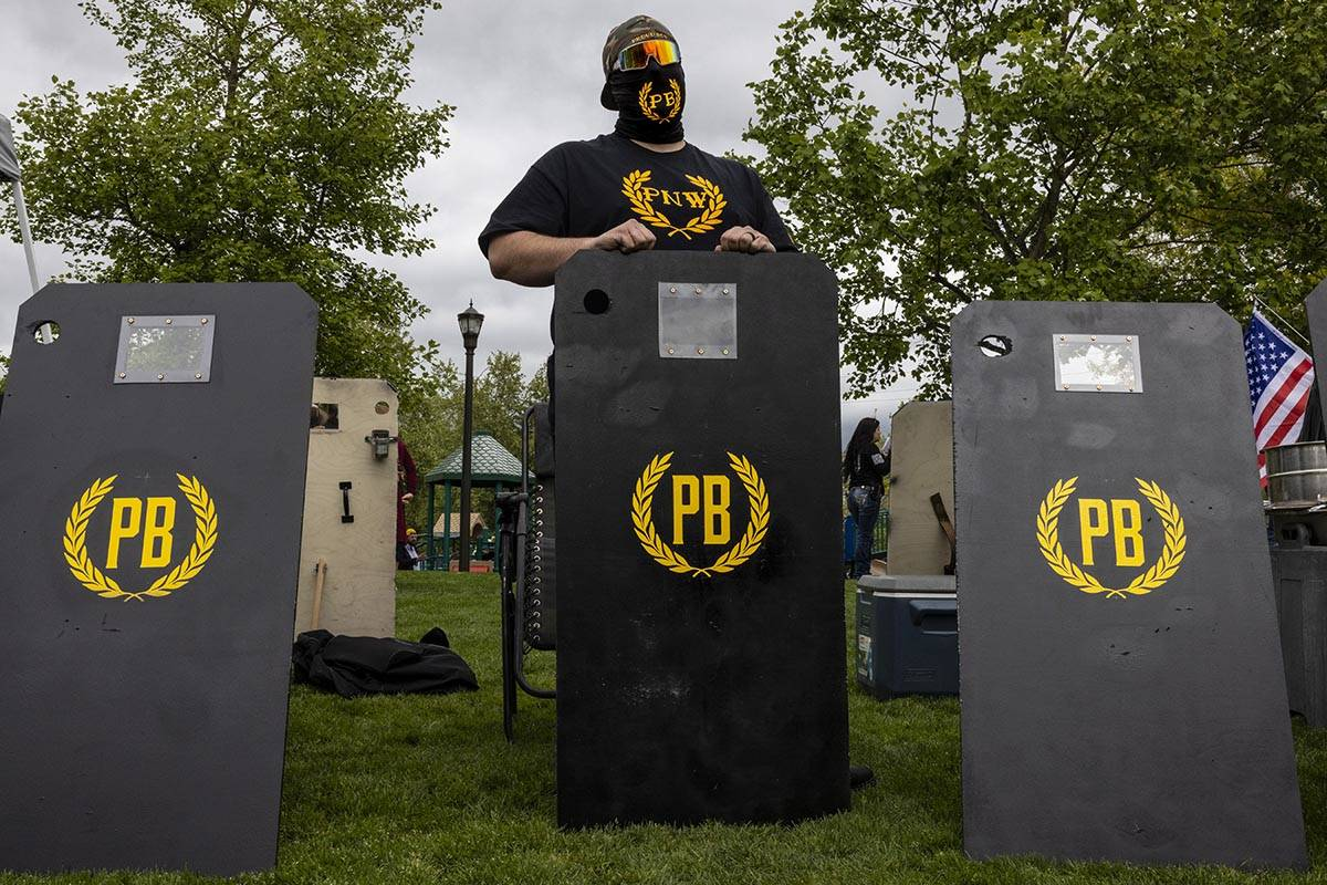 A Proud Boy supporter stands by protective shields as a few hundred people attend a second amen ...