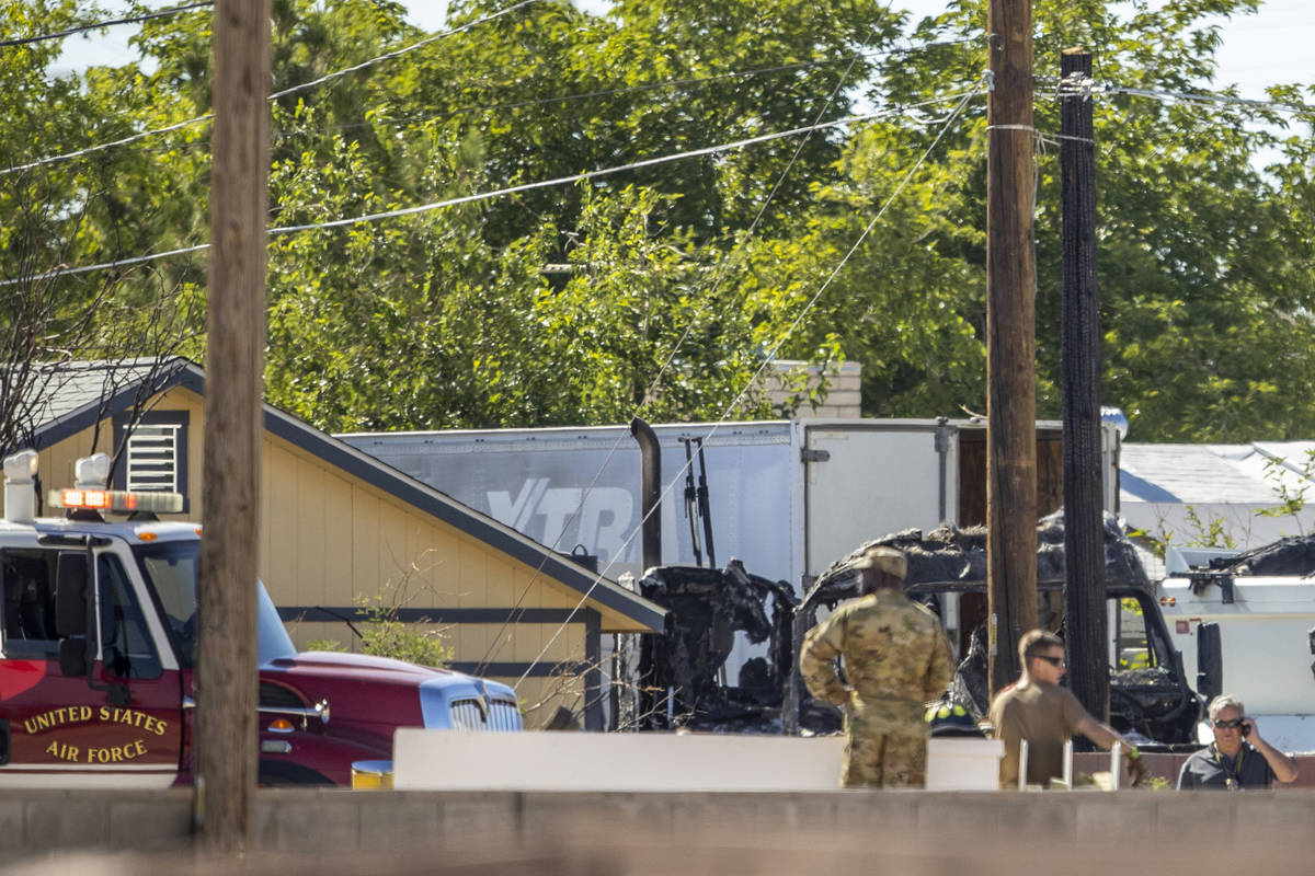 Military personnel look to a burned out vehicle near where a Nellis Air Force Base jet crashed ...