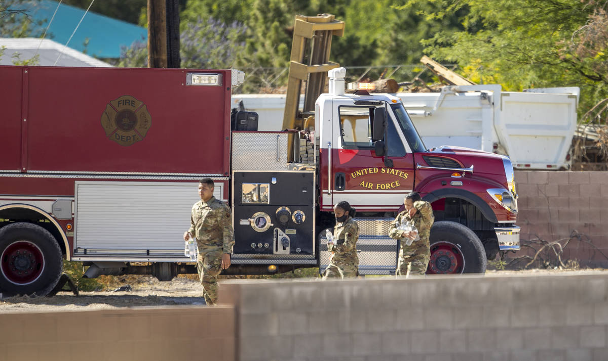 Military personnel walk near where a Nellis Air Force Base jet crashed about Bledsoe Lane on Mo ...