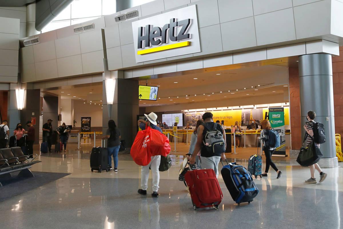 Travelers walk by a Hertz car rental at the McCarran Rent-A-Car Center in Las Vegas, Tuesday, M ...