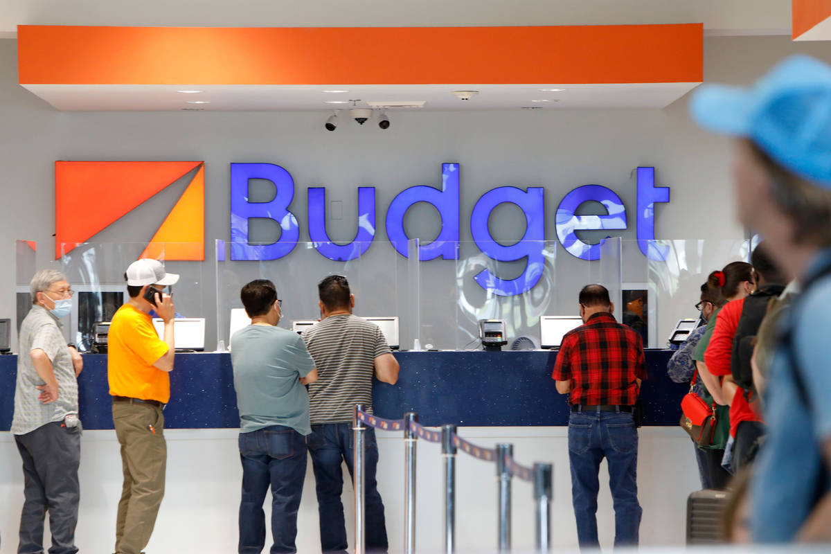 Travelers wait to get a rental car at a Budget car rental in the McCarran Rent-A-Car Center in ...