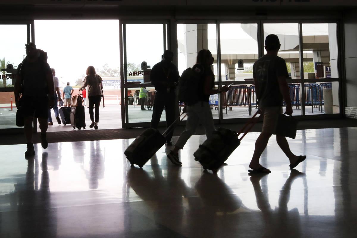 Travelers walk through the McCarran Rent-A-Car Center in Las Vegas, Tuesday, May 25, 2021. (Chi ...
