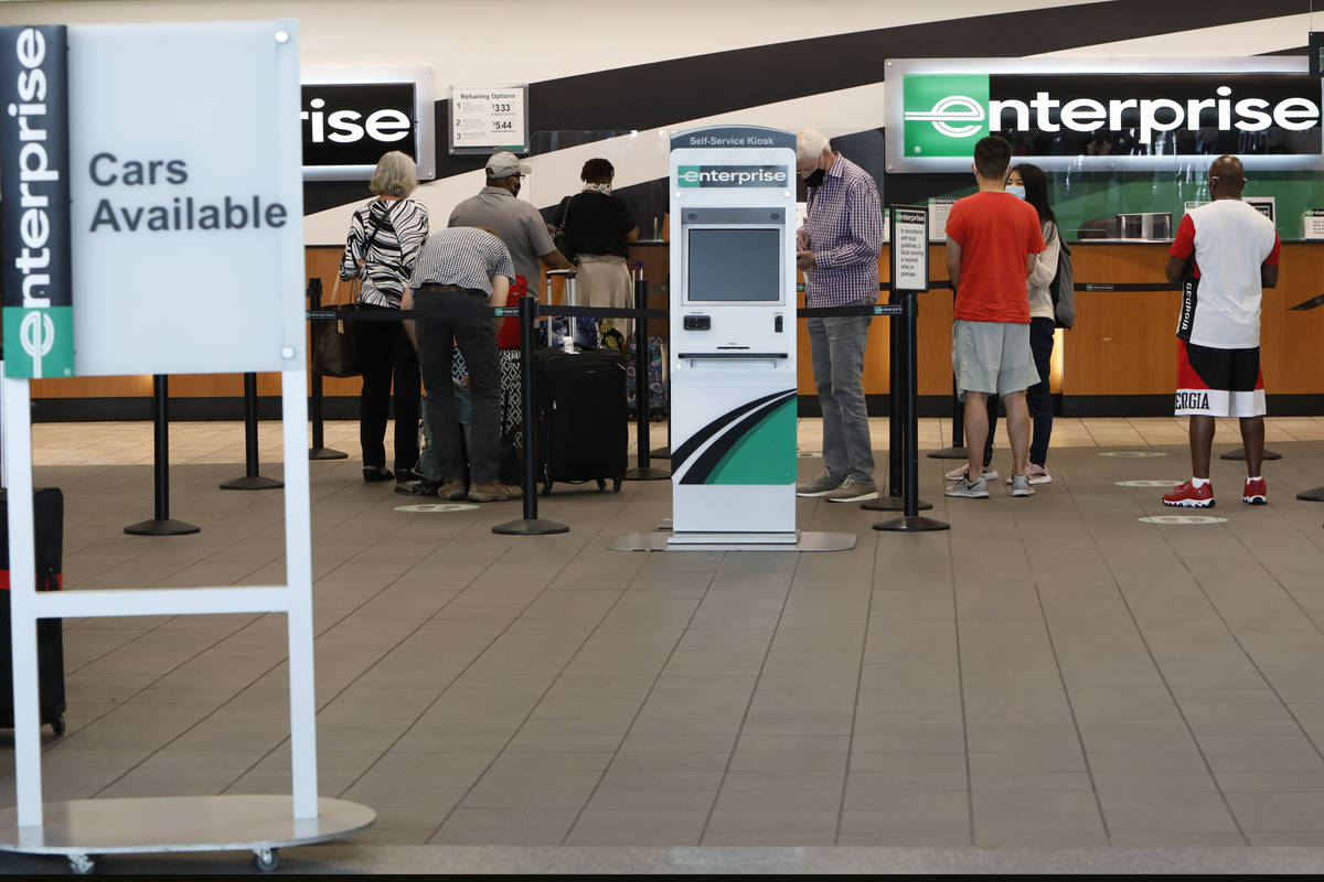 Travelers wait to get a rental car at an Enterprise car rental in the McCarran Rent-A-Car Cente ...