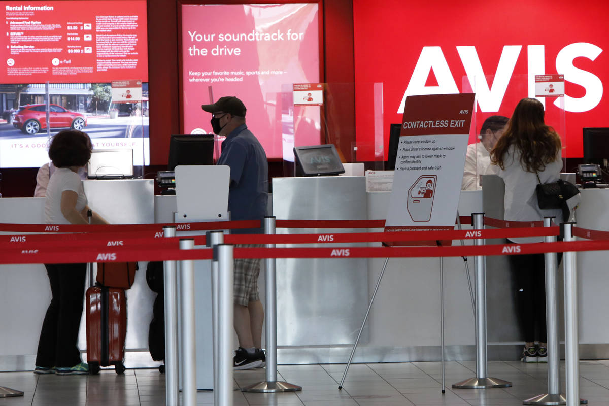 Travelers wait to get a rental car at an Avis car rental in the McCarran Rent-A-Car Center in L ...