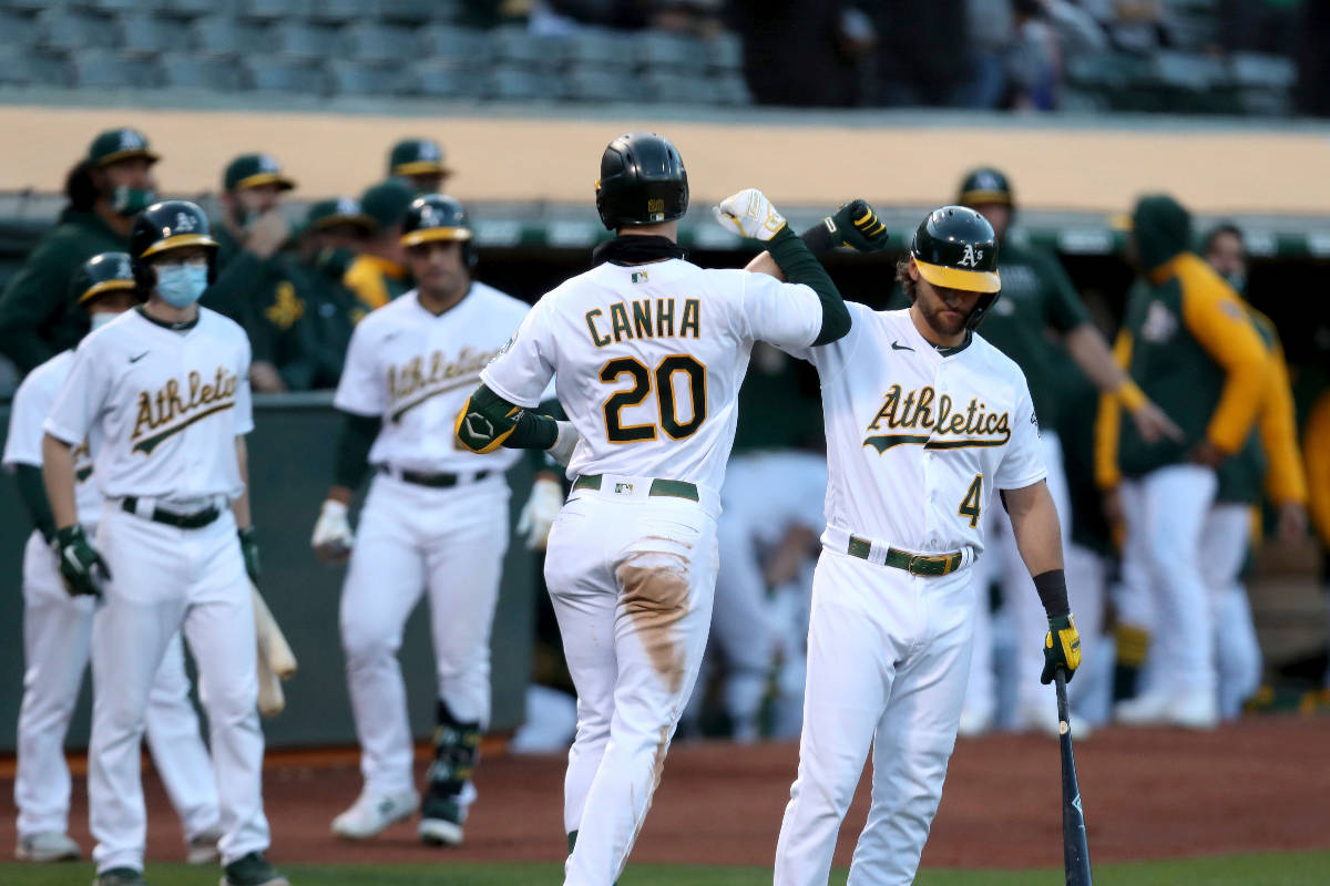 Oakland Athletics' Mark Canha, left, is congratulated by teammate Chad Pinder after hitting a h ...