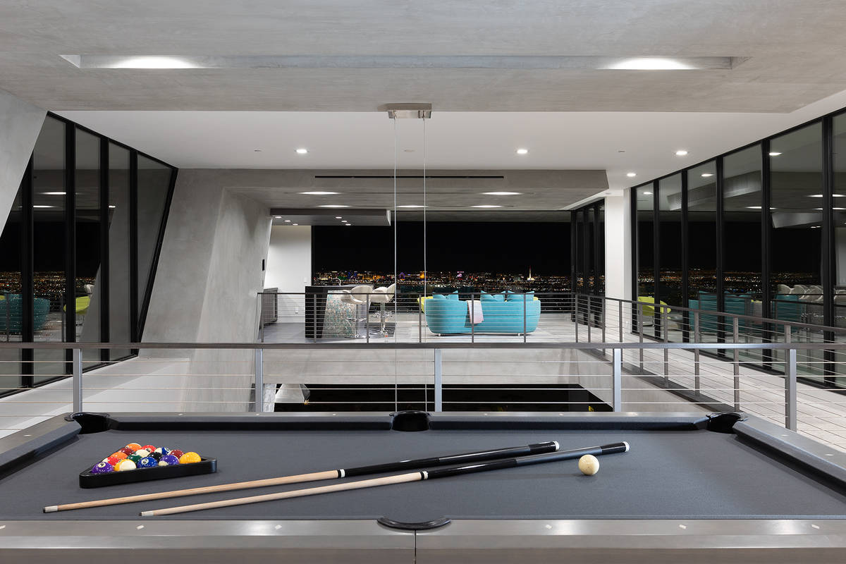 A linear catwalk connects the game room to the bar area, providing views of the main level. (Sy ...