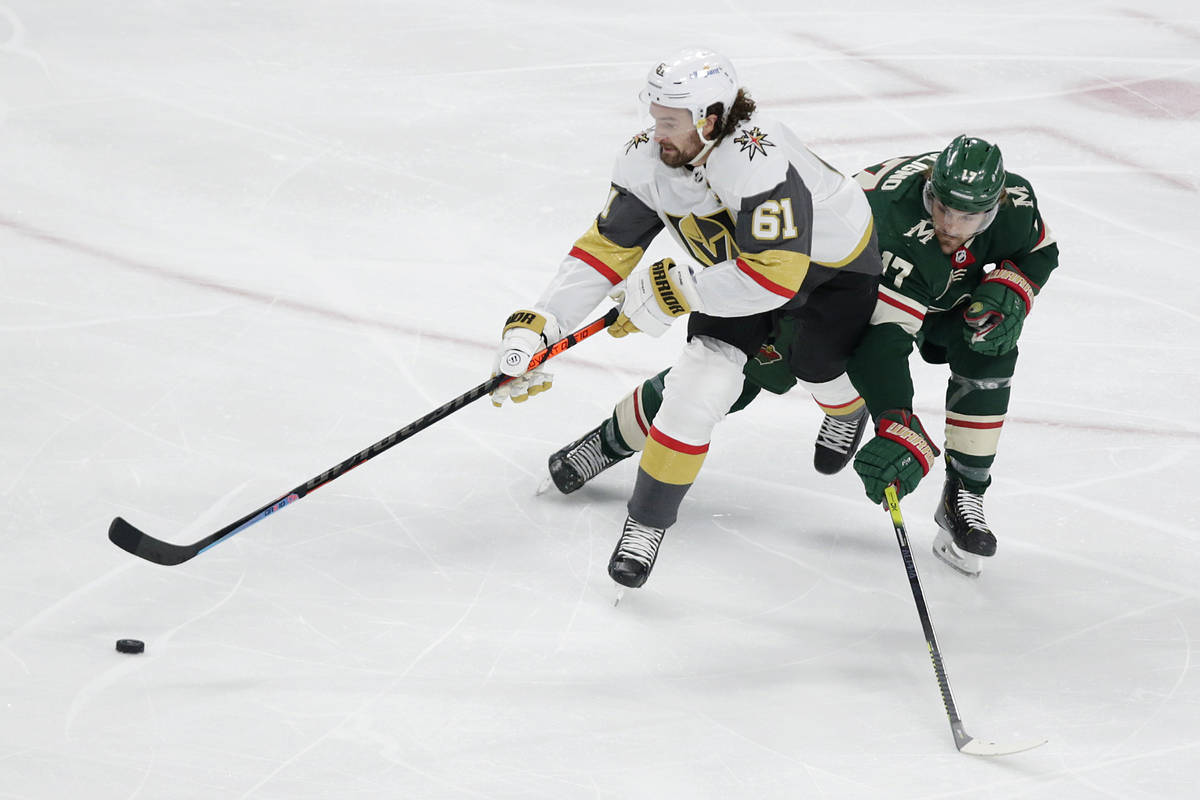 Vegas Golden Knights right wing Mark Stone (61) controls the puck next to Minnesota Wild left w ...