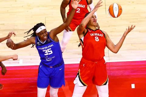 Las Vegas Aces' Liz Cambage (8) grabs a rebound in front of Connecticut Sun's Jonquel Jones (35 ...