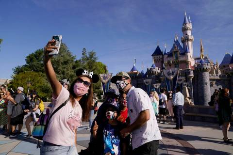 A family takes a photo in front of Sleeping Beauty's Castle at Disneyland in Anaheim, Calif., F ...